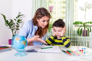 Stressed mother and son frustrated over failure homework, school problems concept. Sad little boy turned away from mother, does not want to do boring homework